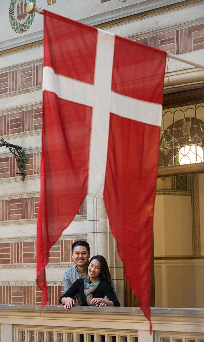 Loving couple smile beneath Denmark flag, photo by TripShooter's Copenhagen photographer Matthew Harrison