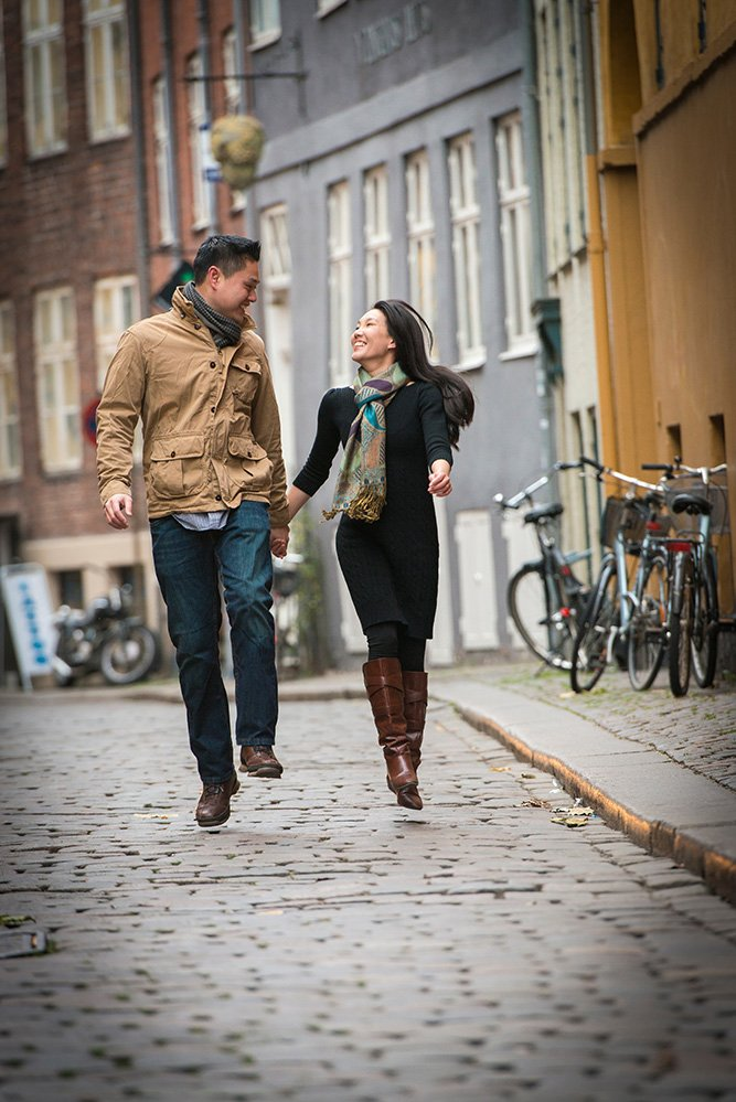 Happy travelling couple run together down Copenhagen street, photo by TripShooter's Copenhagen photographer Matthew Harrison