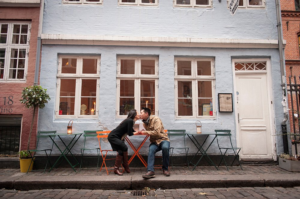 Romantic photo of couple kissing outside Danish cafe while travelling, photo by TripShooter's Copenhagen photographer Matthew Harrison