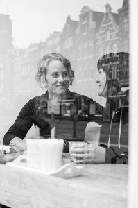 Loving same-sex couple talk in Amsterdam cafe with reflections of the city street, by TripShooter's Amsterdam photographer Cassie Jones
