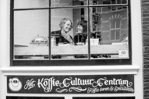 Two women laugh in the window of Amsterdam cafe, photo by TripShooter's Amsterdam photographer Cassie Jones