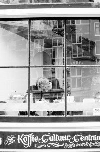 Two women kiss in window of Amsterdam cafe, photo by TripShooter's photographer in Amsterdam Cassie Jones