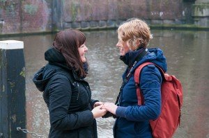 Same sex couple hold hands at Homomonument by the canal, photo by TripShooter's Amsterdam photographer Cassie Jones