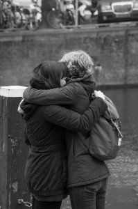 Two girls embrace beside canal in Amsterdam, photo by TripShooter's Amsterdam photographer Cassie Jones