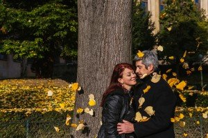 Fun photo of couple in airborne autumn leaves at Trocadero, by TripShooter photographer in Paris Jade Maitre