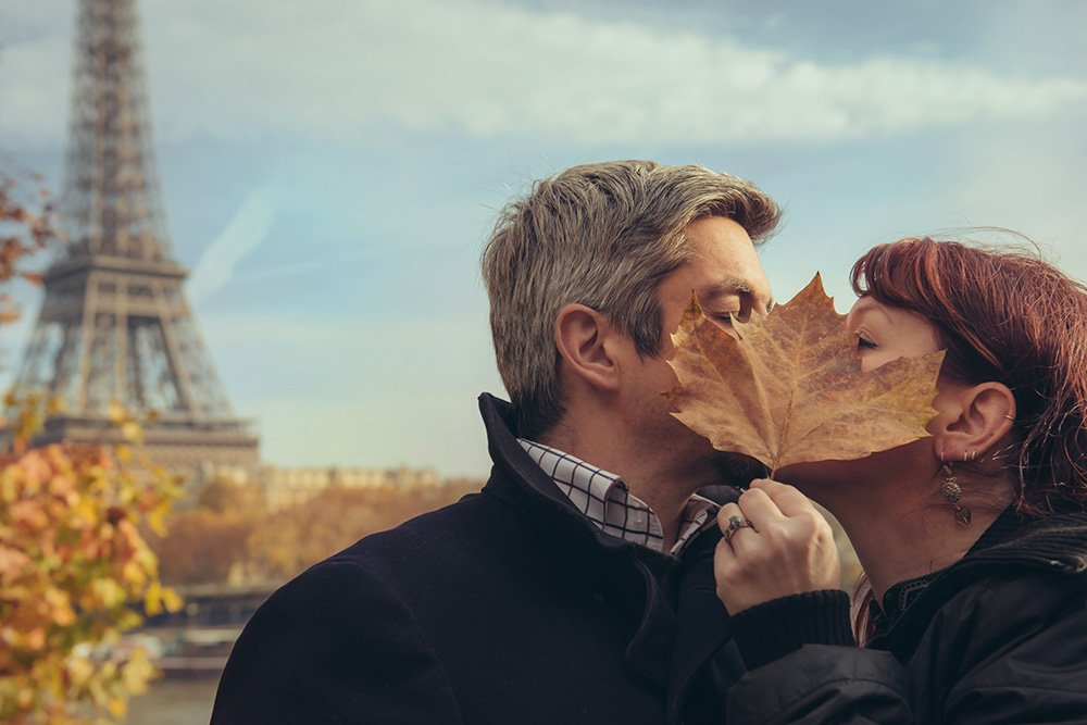 Couple kiss behind an autumn leaf at Eiffel Tower, by TripShooter photographer in Paris Jade Maitre