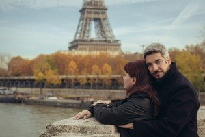 Beautiful portrait of married couple looking over Seine at Eiffel Tower, by TripShooter photographer in Paris Jade Maitre