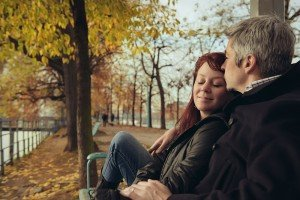 Couple kiss on park bench with autumn leaves, by TripShooter's Paris photographer Jade Maitre