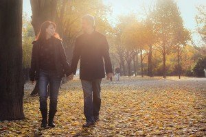 Couple walking through autumn leaves in Paris Champs de Mars, by TripShooter photographer in Paris, Jade Maitre