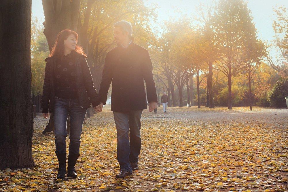 Couple walking through autumn leaves in Paris Champs de Mars, Romantic couple photo session in Paris, by TripShooter photographer in Paris, Jade Maitre