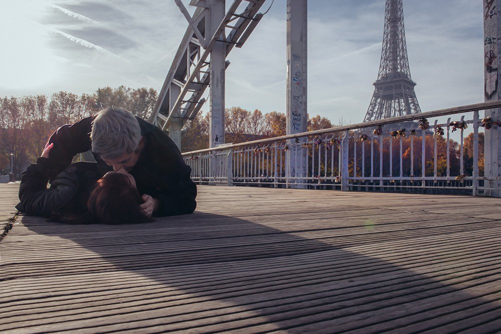 Romantic photo of couple kissing at Debilly bridge in Paris, by TripShooter photographer in Paris Jade Maitre