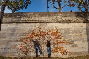 Couple reach for the sky with bright orange autumn vine, photo by TripShooter photographer in Paris Jade Maitre