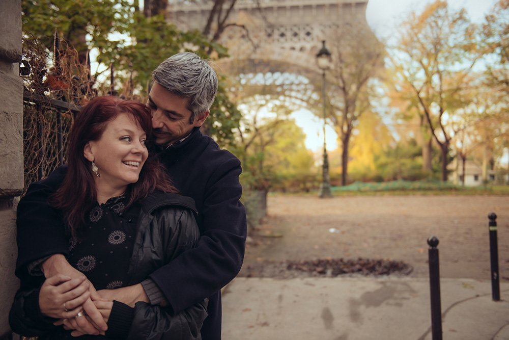 Anniversary couple hug at Eiffel Tower, by TripShooter Paris photographer Jade Maitre