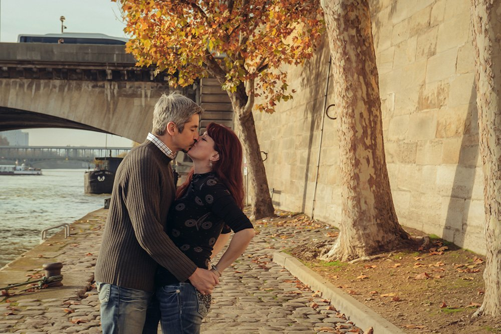 Couple kiss beside the Seine, photo by TripShooter photographer in Paris Jade Maitre