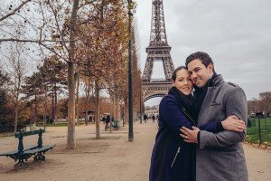 Couple embrace by Eiffel Tower on winter vacation, photo by TripShooter Paris photographer Pierre Turyan.