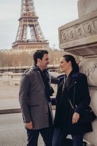 Romantic couple smile on Paris bridge, photo by TripShooter Paris photographer Pierre Turyan