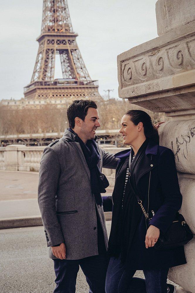 Romantic couple smile on Paris bridge, photo by TripShooter Paris photographer Pierre Turyan