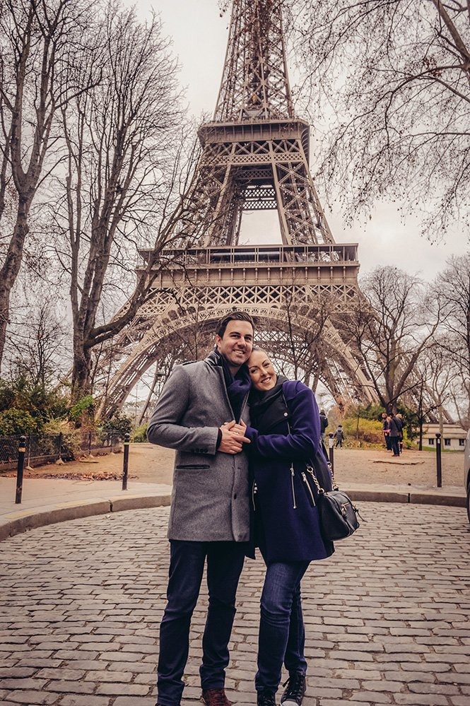 Couple embrace beneath Eiffel Tower, photo by TripShooter Paris photographer Pierre Turyan