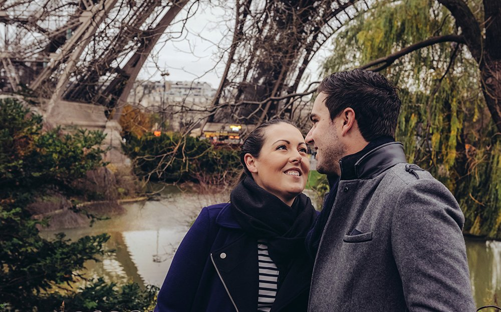 Travelling couple smile beneath the Eiffel Tower in winter, photo by TripShooter Paris photographer Pierre Turyan