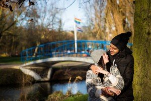 Just engaged couple smile at each other in Amsterdam park, photo by TripShooter's Amsterdam photographer Elena Pasca