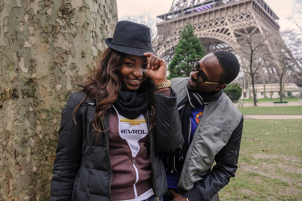 Fun engagement photoshoot of couple with hat in Paris by the Eiffel Tower, photo by TripShooter's Paris photographer Pierre Turyan