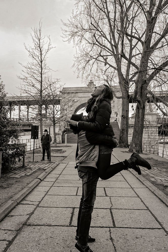 Newly engaged couple jump and embrace with joy in Paris, photo by TripShooter's Paris photographer Pierre Turyan