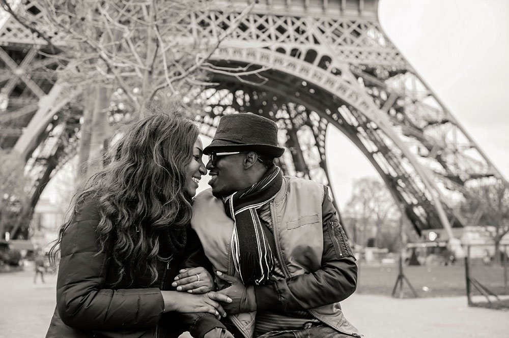 Happy couple embrace beneath the Eiffel Tower, photo byTripShooter's Paris photographer Pierre Turyan
