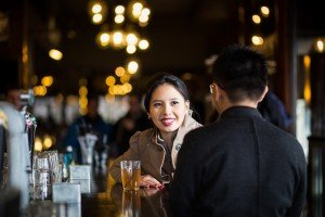 Woman smiles at partner over dutch beer, photo by Elena Pasca TripShooter photographer in Amsterdam