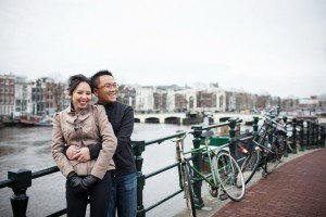 Couple hug by Amsterdam canal, photo by Elena Pasca TripShooter photographer in Amsterdam