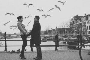 Couple hold hands as seagulls fly around them, photo by Elena Pasca TripShooter's Amsterdam photographer