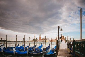 Wedding couple kiss with blue gondolas, photo by TripShooter Venice photographer Jody Riva