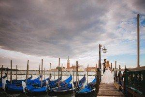 Wedding couple kiss with blue gondolas, photo by TripShooter Venice photographer Jody Riva