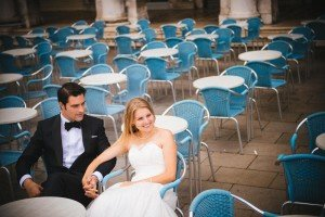 Newlywed couple holding hands on chairs, Wedding couple in Italy dance, photo by TripShooter Venice photographer Jody Riva