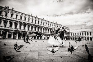 Destination wedding photo of married couple running with pigeons, by TripShooter Venice photographer Jody Riva