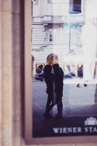 Window reflection of couple in Austria city square - photo by TripShooter's Vienna photographer Evamaria Kulovits
