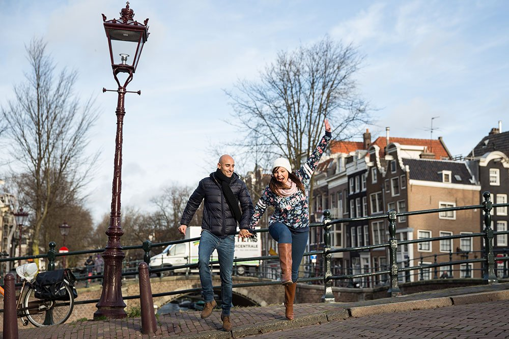 Fun couple play on Amsterdam canal, by TripShooter's Amsterdam photographer Elena Pasca and Radu Voineau