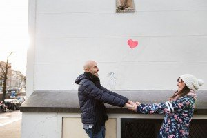 Couple hold hands with love heart street art, by TripShooter's Amsterdam photographer Elena Pasca and Radu Voineau