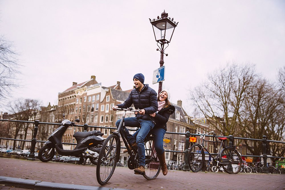 Fun couple ride bike on Amsterdam canal, by TripShooter's Amsterdam photographer Elena Pasca and Radu Voineau