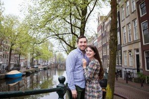 Young travel couple by Amsterdam canal, by TripShooter's Amsterdam photographers Elena Pasca and Radu Voineau