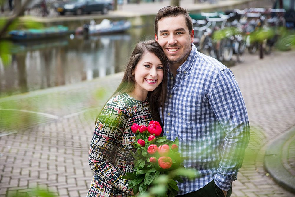 Happy travel couple with tulips by canal, by TripShooter's Amsterdam photographers Elena Pasca and Radu Voineau