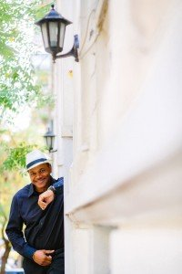 Portrait of happy man with white hat and wall, by TripShooter's Athens photographer Andreas Stavropoulos