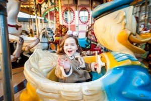Happy child on carousel, by TripShooter's photographer in Santiago de Compostela, Bertolino Matteo