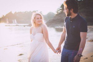 Bride smiling and holding hands with groom on beach, photo by Mont St Michel France photographer Frederic Renaud