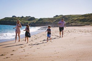 Family photo session running on beach in Normandy France, by Mont St Michel photographer Frederic Renaud