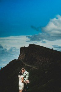 Kissing couple with cliffs on romantic photoshoot in Scotland, by TripShooter's Edinburgh photographer Sean Bell
