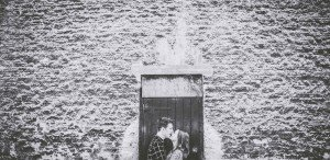 Couple kissing in front of old wall, by TripShooter's Edinburgh photographer Sean Bell