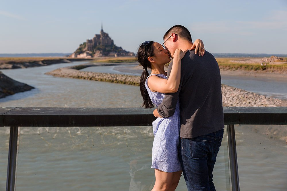 Couple kiss after marriage proposal in Mont St Michel France with TripShooter photographer Frederic Renaud