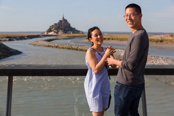 Couple laugh after romantic marriage proposal in Mont St Michel France with TripShooter photographer Frederic Renaud