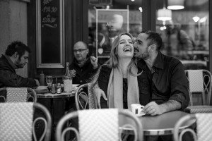 Laughing couple kiss in Paris cafe, photo by TripShooter's photographer in Paris, Christian Perona