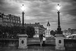 Romantic photo of couple on Paris bridge at dusk, photo by TripShooter's photographer in Paris, Christian Perona